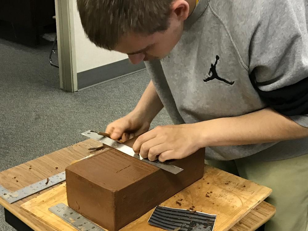 student cutting clay